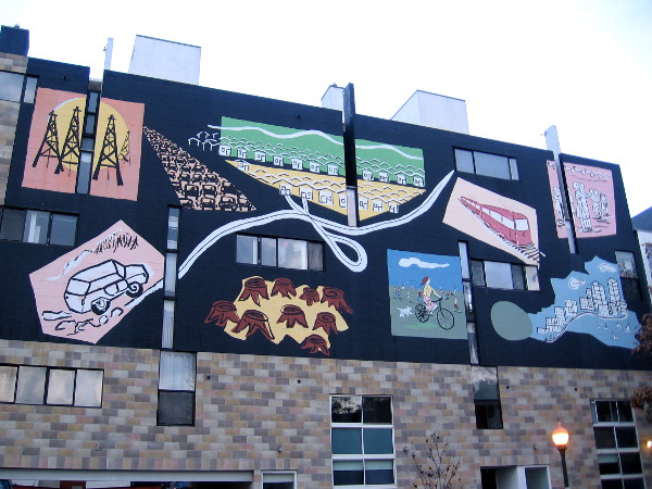 A large mural on a building that can be seen from nearby Interstate 5. Colorful images seem to convey an environmental message, encouraging bike riding and public transit.