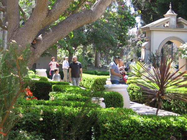 People walk through Balboa Park's sunlit Alcazar Garden on a beautiful spring Sunday.