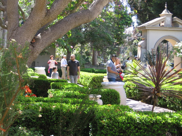 People walk through Balboa Park's sunlit Alcazar Garden on a beautiful spring Sunday.