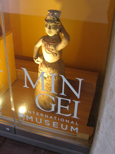 A clay female figure on display in one glass case outside the entrance to the Mingei International Museum.