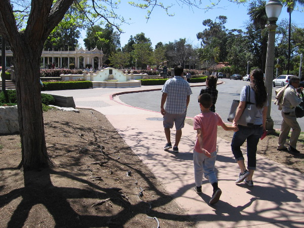 A family walks toward the Spreckels Organ Pavilion. It's a perfect spring day to be outside in San Diego.