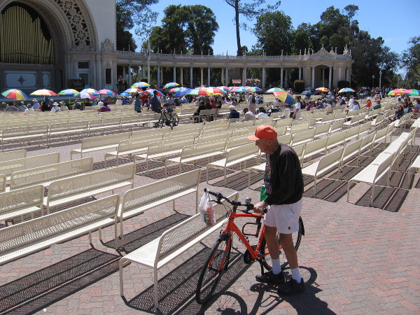 A bicyclist has arrived for the two o'clock Sunday organ concert in Balboa Park, which is always free.