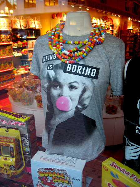 A t-shirt proclaims Being Normal is Boring in the window of It's Sugar.