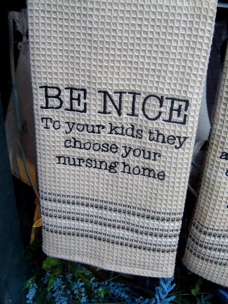 A dish towel at Bubbles Boutique reminds everyone to be nice to your kids--they choose your nursing home.