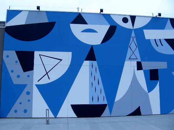 Left half of mural by Rafael Lopez outside Coasterra on Harbor Island seems to depict abstract boats and the San Diego skyline across the bay.