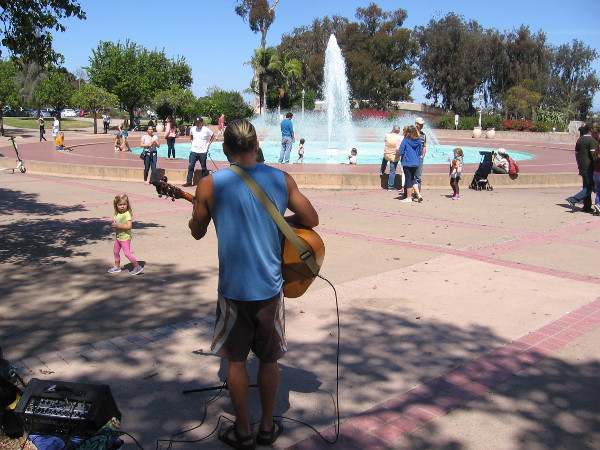 A guitarist plays in some shade near the splashing Bea Evenson Fountain in the Plaza de Balboa.
