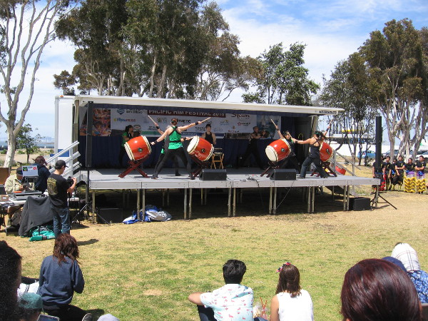 An audience has gathered at the stage to watch energetic drumming by Naruwan Taiko.