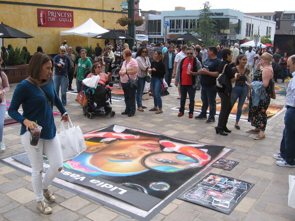 People gather around chalk art created on boards for the 2018 Mission Federal ArtWalk in Little Italy.