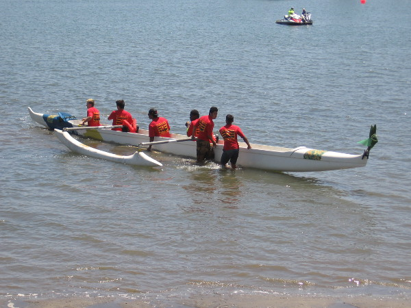 A team walks their outrigger canoe out into Mission Bay.