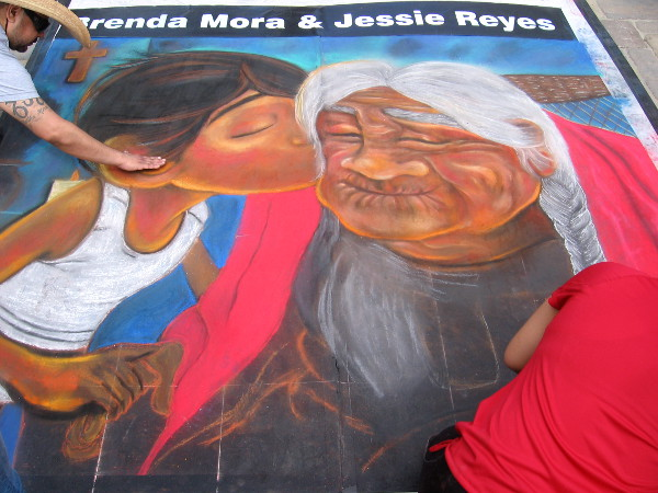 Young girl kisses a happy wrinkled woman. Touching chalk art by Brenda Mora and Jessie Reyes.