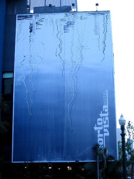Mural on side of Porto Vista Hotel shows reflections of sailboat masts in blue water.