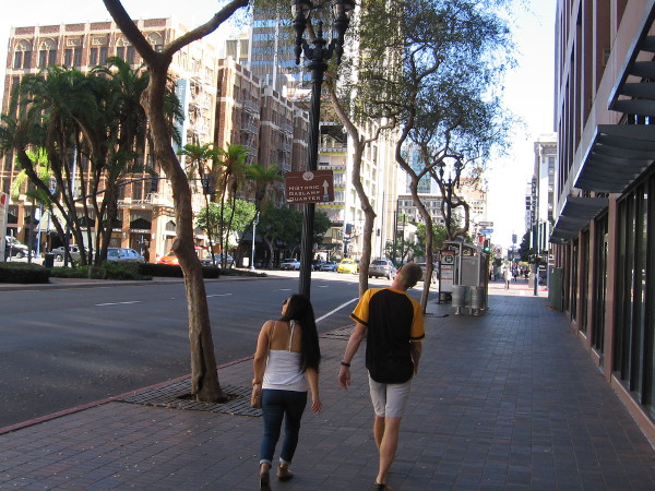 A couple walks along Broadway in downtown San Diego.