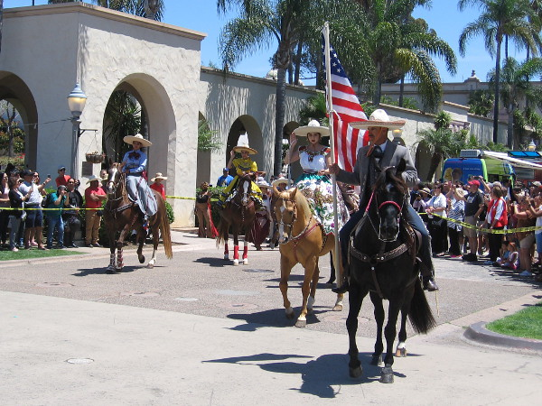 Riders on horseback wear various traditional costumes. The caballero with the American flag is in the gala dress of a charro.