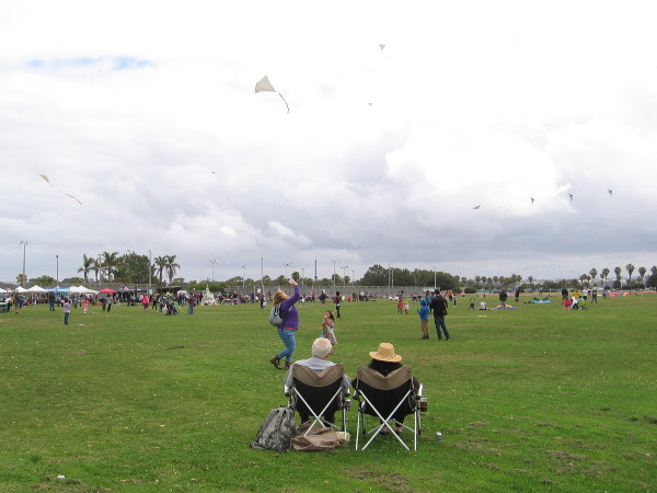 A couple has front row seats to a lot of colorful kite action at Robb Field in OB.