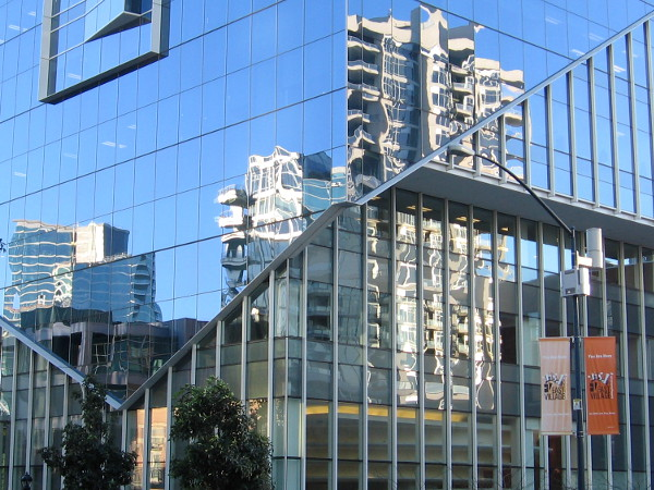 Buildings in East Village reflected in the glass windows of the headquarters of Sempra Energy.