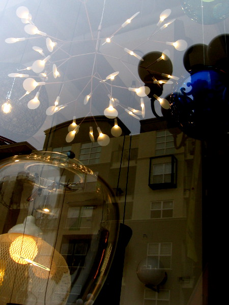 Light fixtures mingle with reflections. Magic in one window of Urban Lighting.
