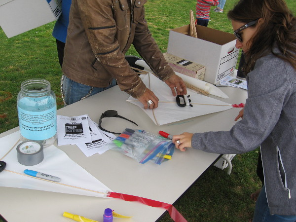 Materials at a kite creation and repair station include markers to add color to new kites.