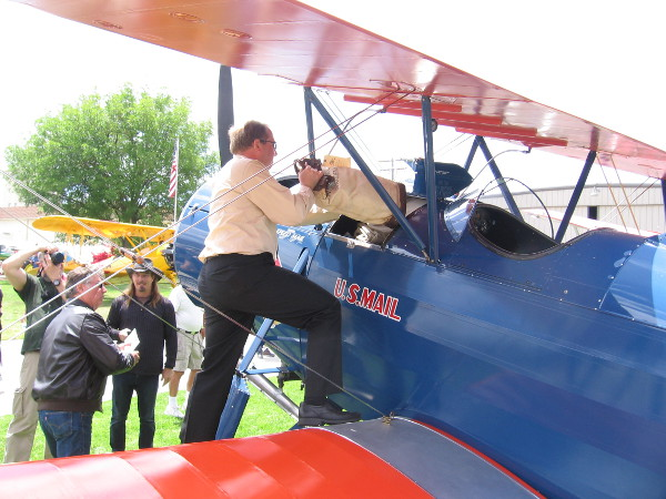 Loading a sack of official U.S. Mail into a cockpit of one Stearman Speedmail biplane.