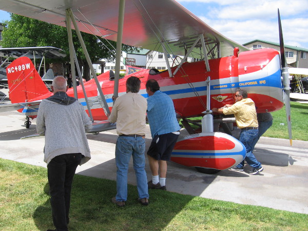 People roll the biplane off the grass so that it can taxi away from the Allen Airways Flying Museum.