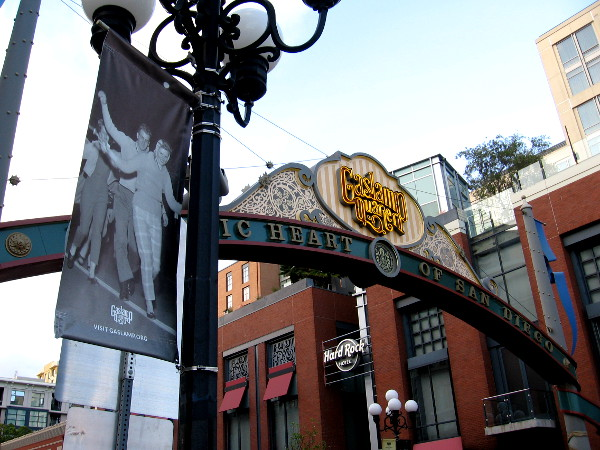 A banner hanging on a lamppost near the Gaslamp Quarter landmark sign shows a fun photo from San Diego history.