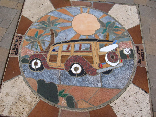 A woodie with surfboard under palm trees and a shining sun. This mosaic greets people walking down the sidewalk in Solana Beach.