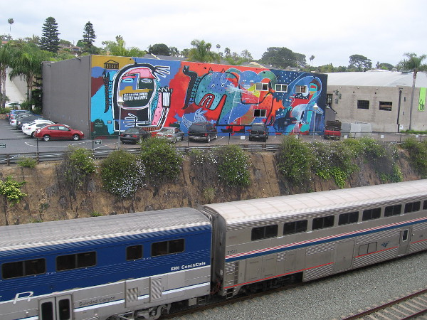 An Amtrak Pacific Surfliner train heads south, passing a cool mural titled Myths at Play, just south of the Solana Beach station.
