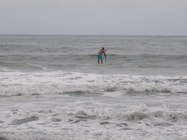 A stand up paddle surfer was out on the Pacific Ocean looking for the perfect wave.