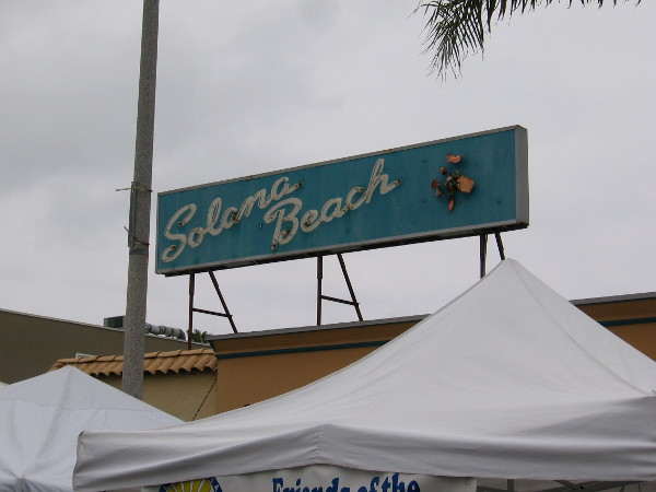 A cool Solana Beach sign above the tops of tents at Fiesta del Sol.