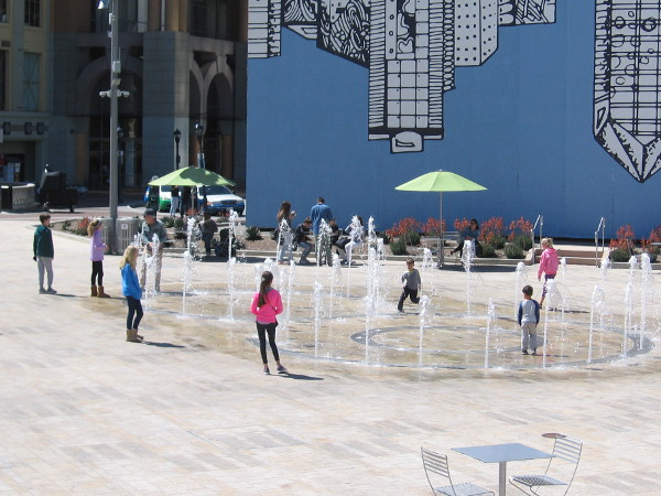 People play in the fun, splashing fountain at Horton Plaza Park.
