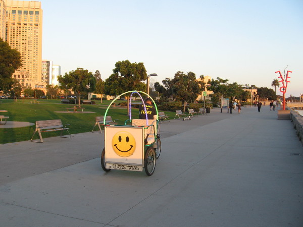 Smiley face on a pedicab heads toward four Urban Trees. The Port of San Diego public sculptures were recently moved from the Cruise Ship Terminal to Ruocco Park.