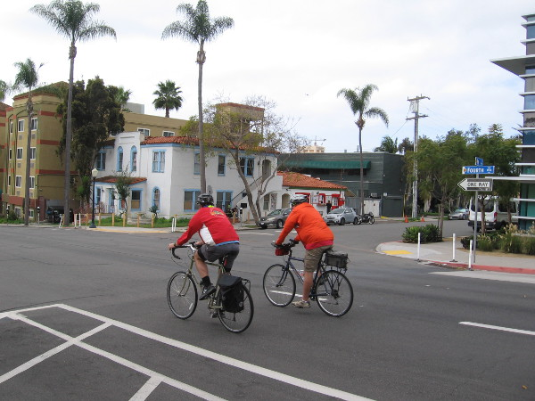 Some guys ride their bikes down Fourth Avenue through Bankers Hill.