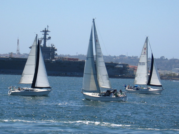 Three sailboats pass the USS Theodore Roosevelt (CVN-71) aircraft carrier docked at Naval Air Station North Island.