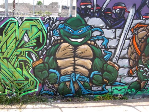 Leonardo, leader of the Ninja Turtles, stands alert beside some bold, colorful graffiti.