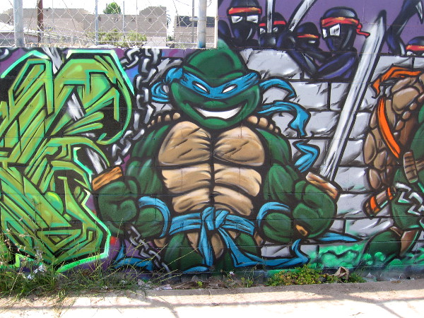 Leonardo, leader of the Ninja Turtles, stands alert beside some bold, colorful graffiti.