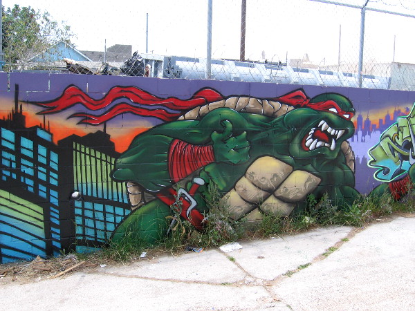 Raphael emerges from a spray painted city. This particular turtle does not appear to be amused.