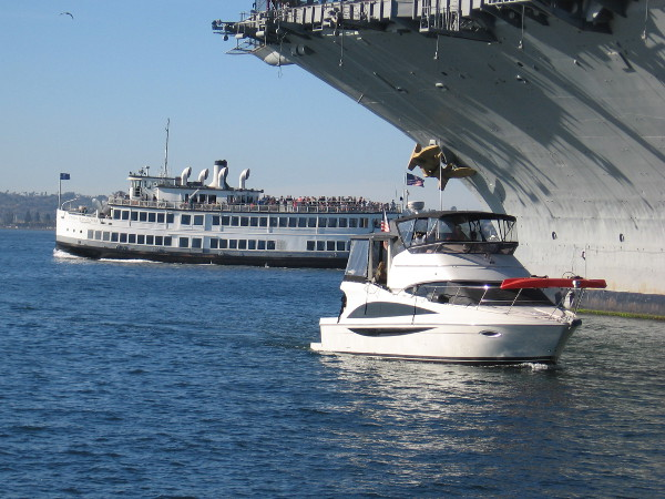 The Admiral Hornblower and another boat pass near the bow of the USS Midway Museum, recently deemed the best attraction in California.