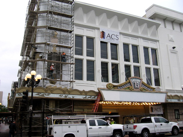 Workers beautify a building that will be home to a luxury theater and two new restaurants.