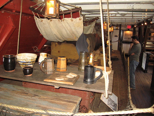 A suspended mess table where sailors would eat together next to a hammock on the gun deck of HMS Surprise.