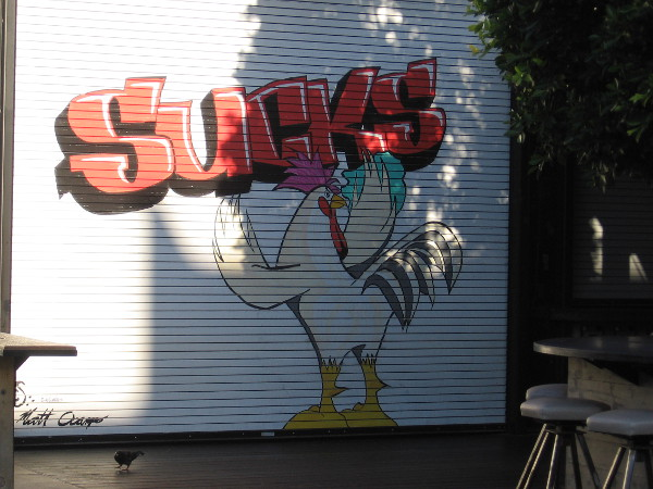 A street art chicken spray paints graffiti on a restaurant door.