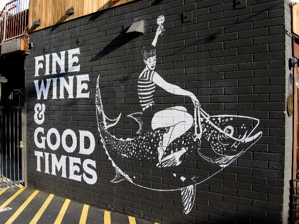 Riding a fish with wine glass raised high.