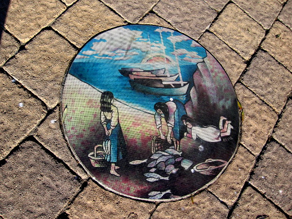 A colorful circle of artwork on the nearby sidewalk shows women with baskets and bountiful fresh fish.