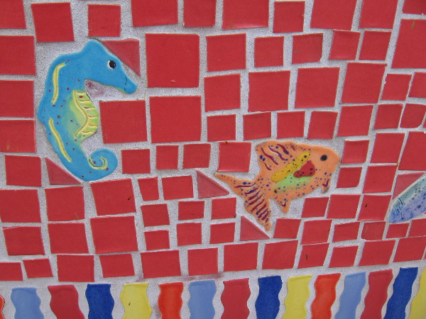 Small sea creatures made of ceramic swim about a tile mosaic bench at a bus station in Solana Beach.