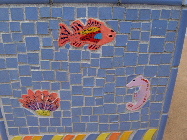 A colorful fish, shell and seahorse among small blue tiles.