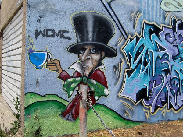 The Mad Hatter in street art at one end of a Logan Heights alley.