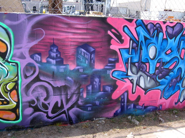 A section of bold urban art on a long wall.
