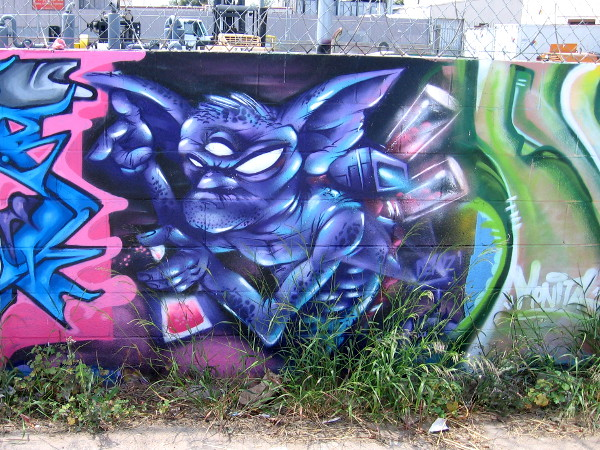 A wicked-looking character seems to be spray painting the graffiti next to him.