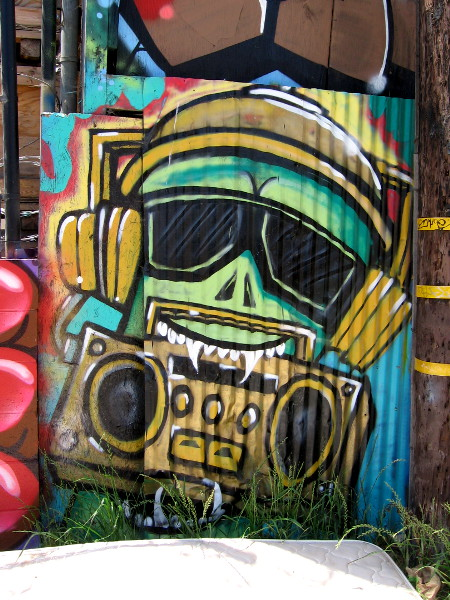 A character with sunglasses and headphones holds a boombox with his fang-like teeth.