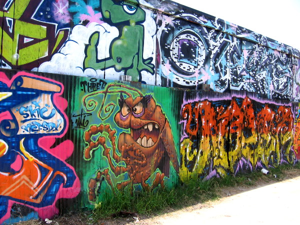 Elaborate urban artwork completely covers a long alley wall in Logan Heights.