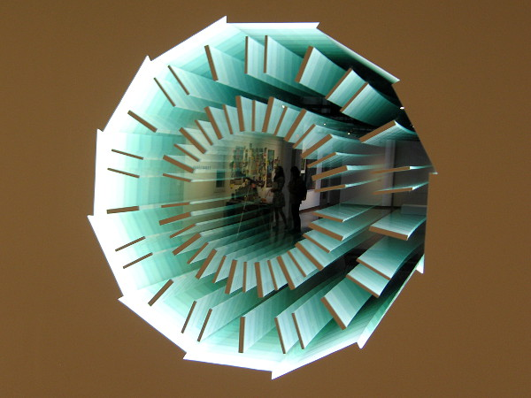 Art that creates an infinite reflection and contemplates the scale and structure of space and time. The two-way mirror is titled Down the Rabbit Hole (CMS Detector) by artist Adam Belt.