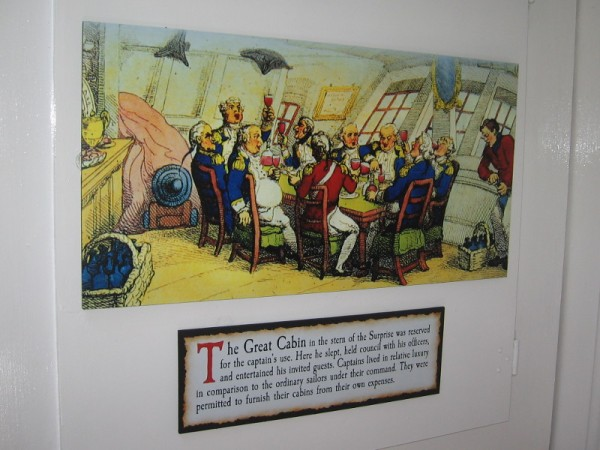 Sign reads the Great Cabin in the stern of the Surprise was reserved for the captain's use. Here he slept, held council with his officers, and entertained his invited guests.